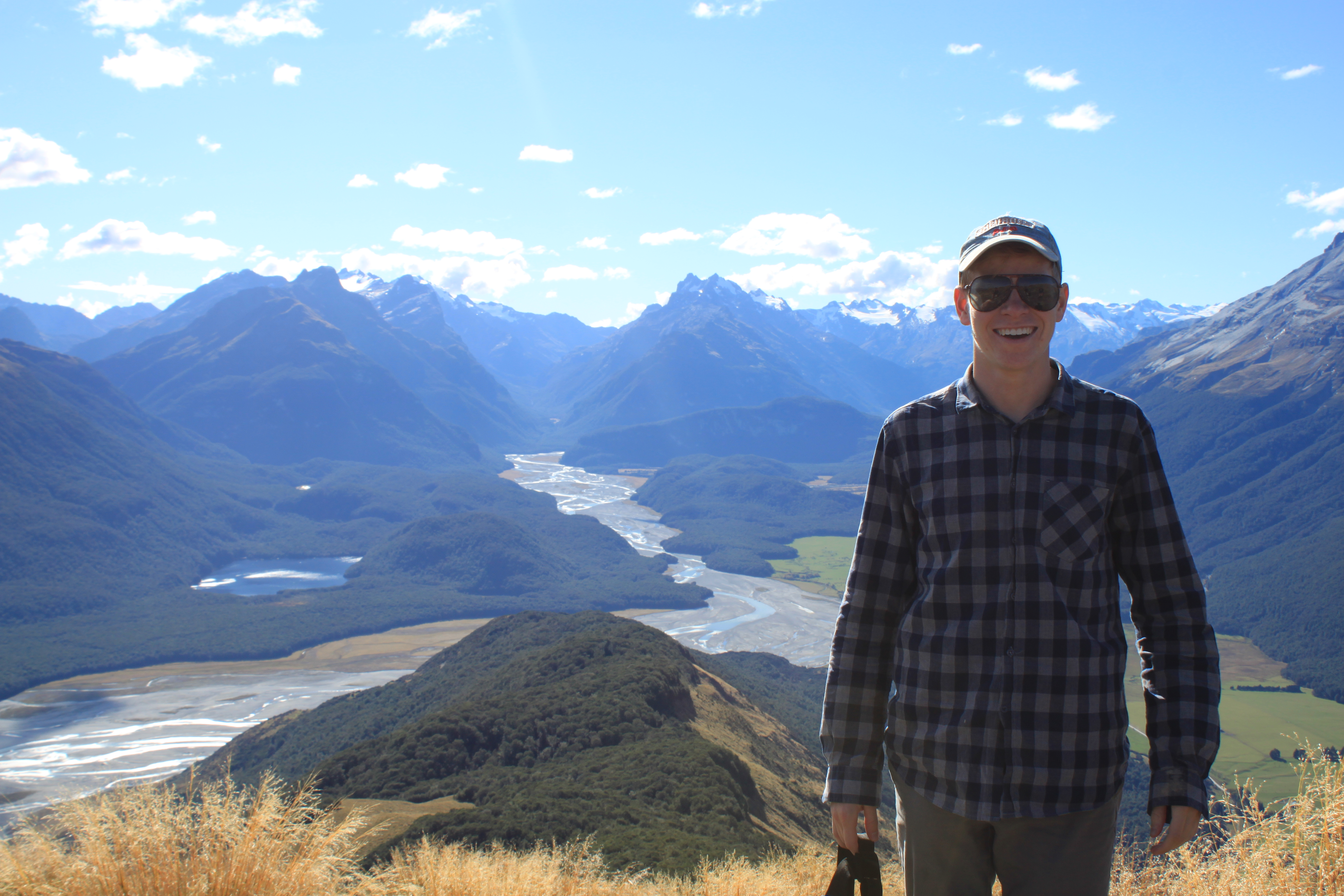student posed in front of mountain range